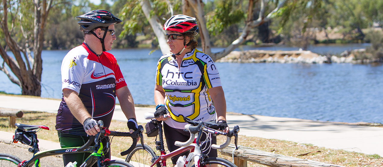 cyclists-talking-with-a-river-in-the-background