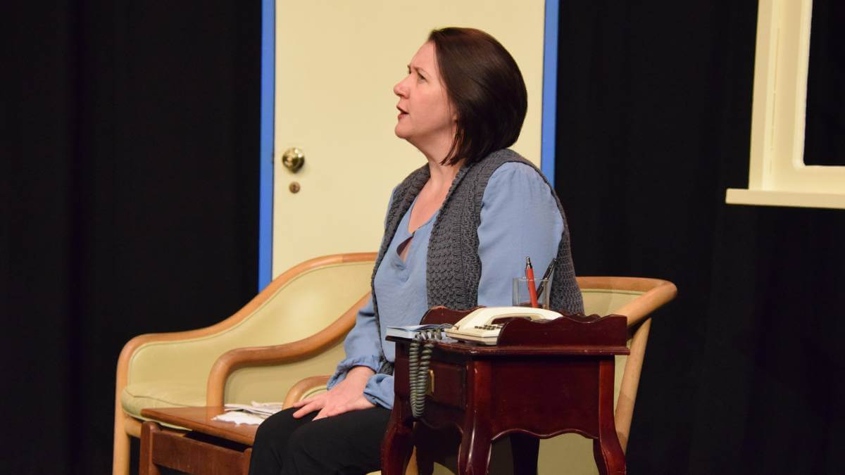 Photo of Sharon Pegrum seated on stage in a scene from Proposals at the Link Theatre in Northam. Photo credit: The Avon Valley Advocate.