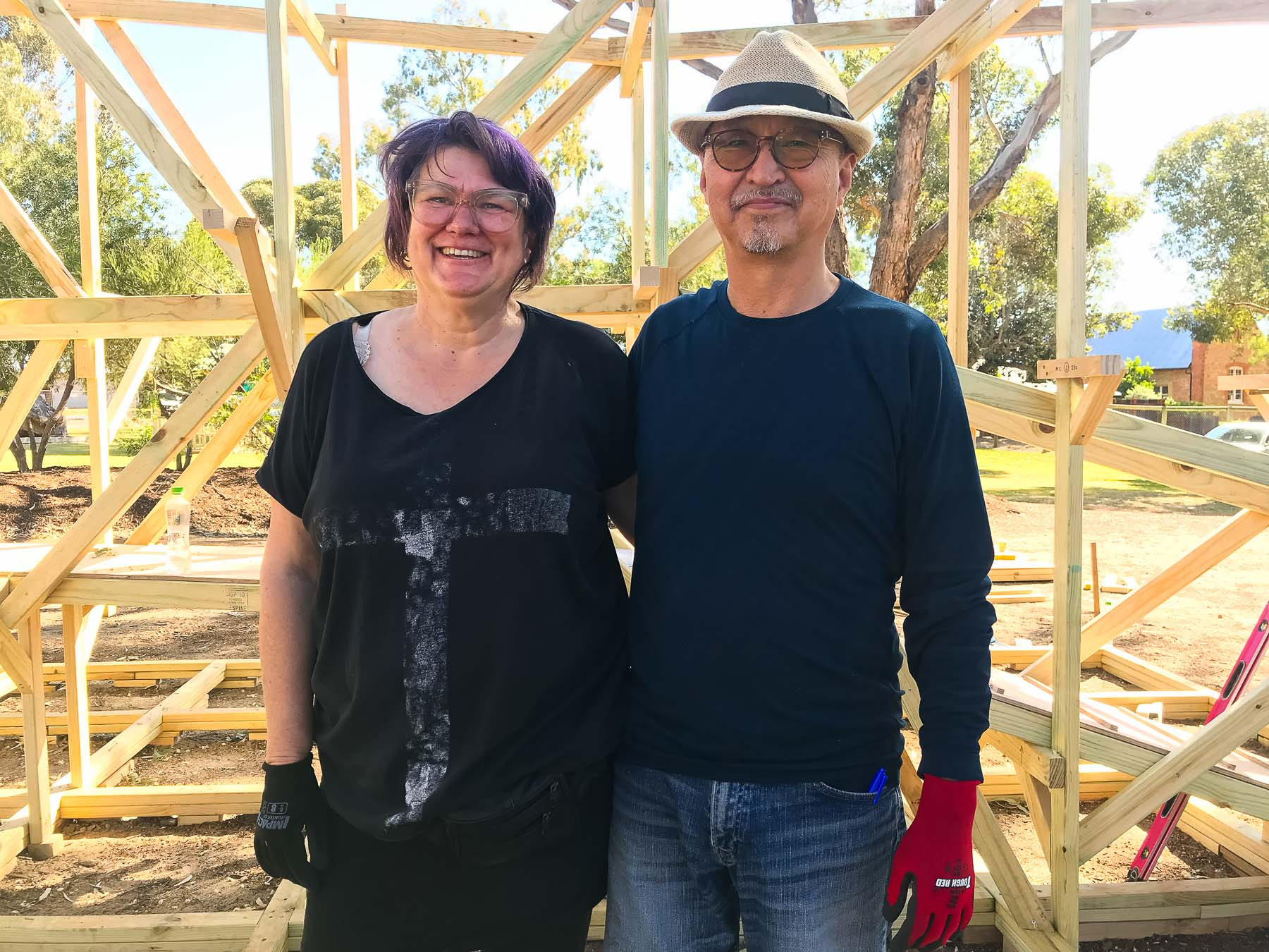 photo of two artists side by side in front of timber framework. Photo by Caro Telfer.